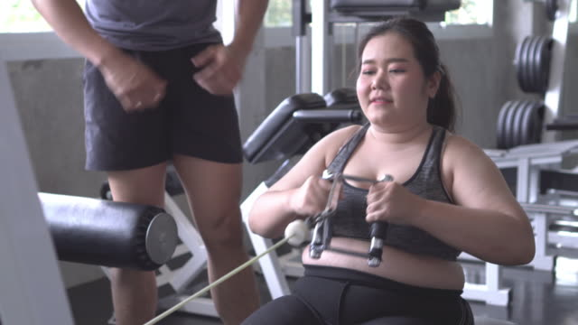 overweight girl using machine in fitness side view - addition key stock videos & royalty-free footage