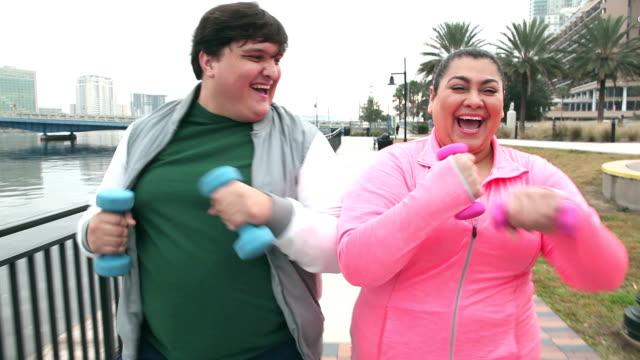 overweight hispanic couple having fun exercising - racewalking stock videos and b-roll footage