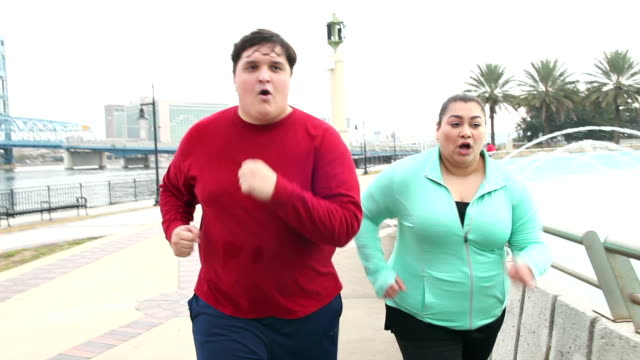 overweight hispanic couple jogging together - overweight stock videos and b-roll footage