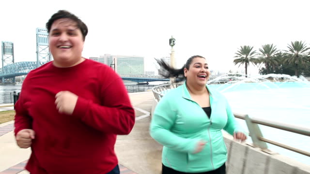 overweight hispanic couple jogging together - overweight active stock videos & royalty-free footage