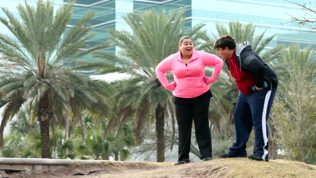 Overweight Hispanic couple jogging together