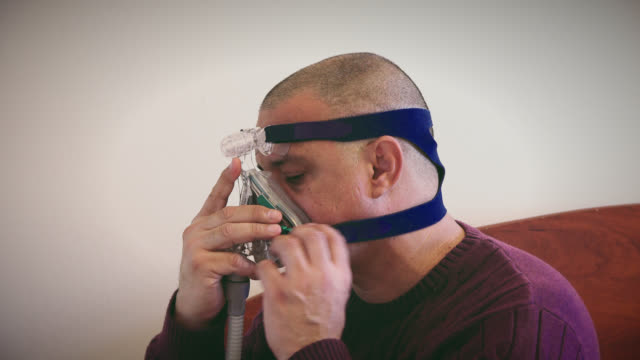 overweight hispanic man suffering from sleep apnea - 無呼吸点の映像素材/bロール