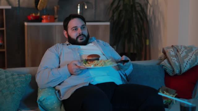 vídeos y material grabado en eventos de stock de sobrepeso a hombre cambiando los canales - colesterol