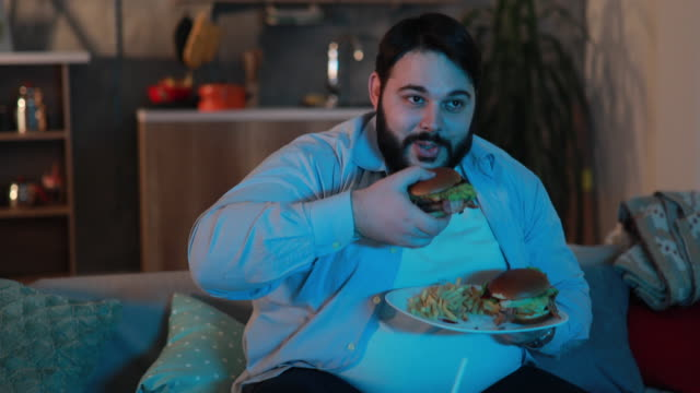 Overweight man eating unhealthy dinner