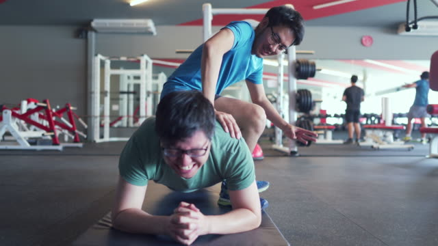 overweight man holding plank position in fitness/gym under his friend's supervision, got teased by his friend - belly button piercing stock videos & royalty-free footage