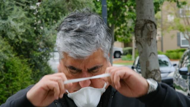 彼の顔に彼の顔に置く太りすぎの男は、非常事態のcovid-19状態による本当のn95保護マスク - レスピレーターマスク点の映像素材/bロール