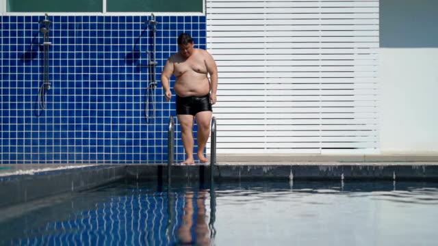 slo mo - overweight man shower before getting into swimming pool - pantaloncino da bagno video stock e b–roll
