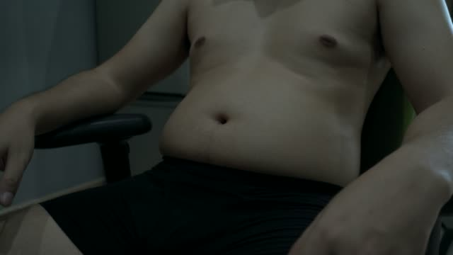 Übergewichtiger Mann sitzt auf einem Stuhl, betont die eigene Form