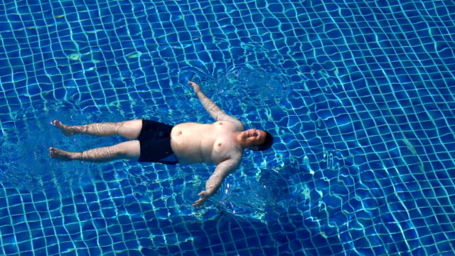 slo mo - overweight man swimming starfish float in swimming pool - attività del fine settimana video stock e b–roll
