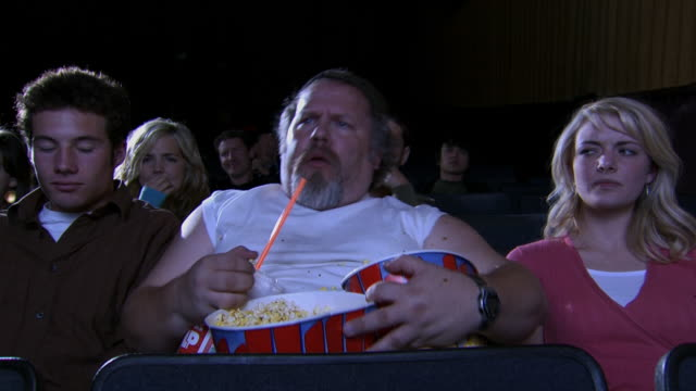 Overweight man with popcorn at movie theatre with young couple