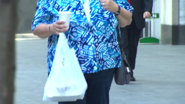 overweight people walking with food - overweight stock-videos und b-roll-filmmaterial