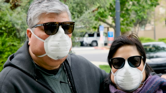 overweight senior couple wearing a n95 protective mask due covid-19 pandemic - minoranza video stock e b–roll