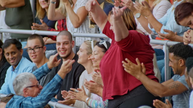 slo mo overweight woman dancing on the stadium tribune and having a great time - overweight stock-videos und b-roll-filmmaterial