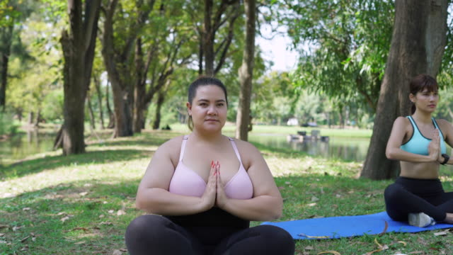 overweight woman doing yoga at park - overweight yoga stock videos & royalty-free footage
