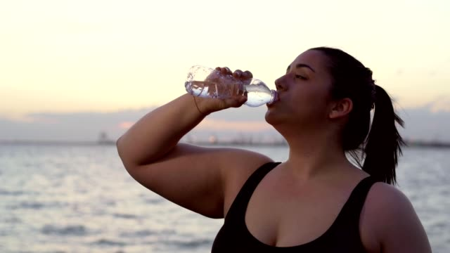 Overweight woman drinking water