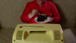 Overweight woman eating cake and watching vintage TV