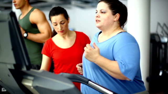 Overweight woman exercising on a treadmill.