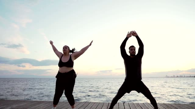 Overweight woman exercising with trainer