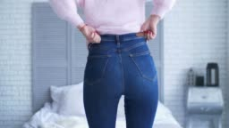 Overweight woman fitting in tight jeans in bedroom