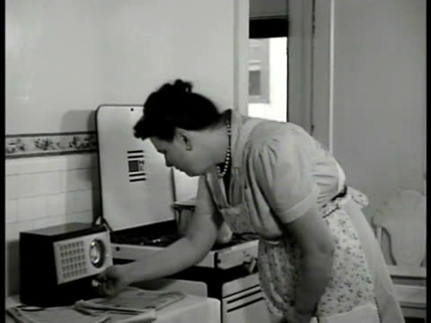 Overweight woman in dress apron standing in front of stove looking at radio on counter adjusting dial on small radio CU Female hand turning radio dial