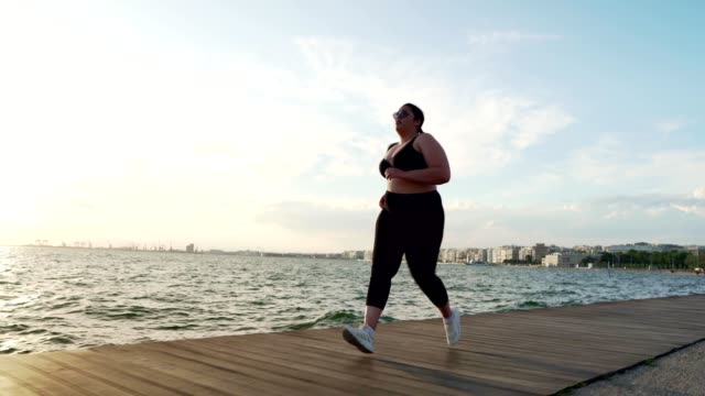 overweight woman jogging - body positive stock videos & royalty-free footage