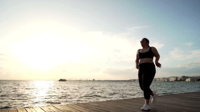vídeos y material grabado en eventos de stock de mujer con sobrepeso corriendo - overweight