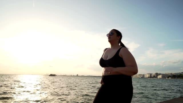 vídeos y material grabado en eventos de stock de mujer con sobrepeso corriendo - corredora de footing