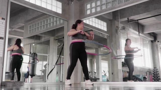 (slow motion) overweight woman play hula hoop in fitness gym. - corporatura larga video stock e b–roll