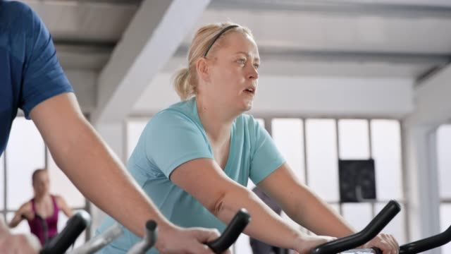 Overweight woman riding indoor bicycles in the fitness center