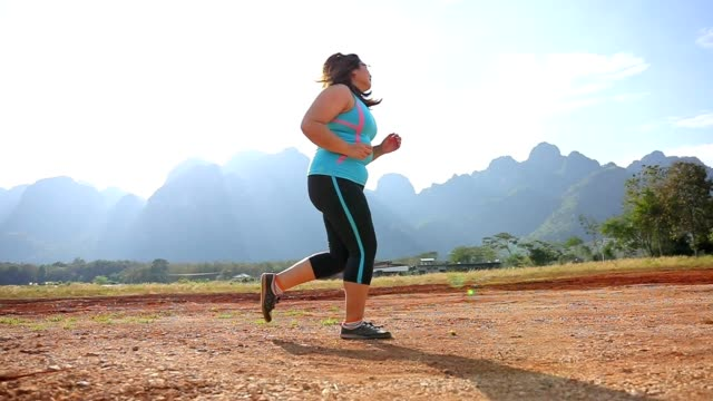 vídeos de stock e filmes b-roll de overweight woman running in park in the morning slow motion - gordo