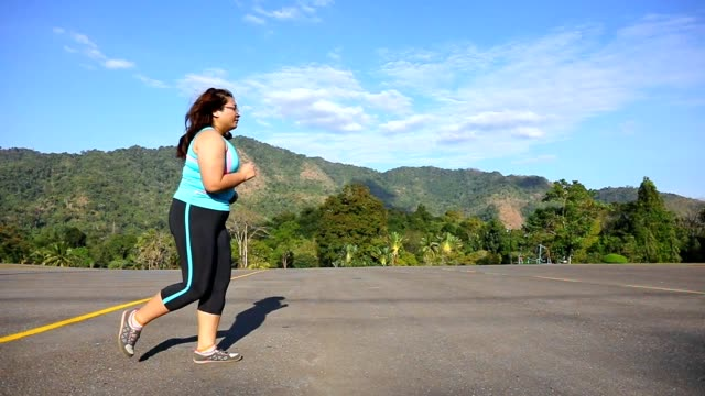vídeos de stock e filmes b-roll de overweight woman running in park in the morning slow motion - plus key