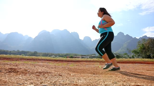 Overweight woman running in park in the morning