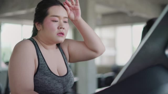 vídeos de stock, filmes e b-roll de mulher com sobrepeso correndo escadas rolantes exercício de treino cardio no ginásio de fitness. - peso livre equipamento para exercícios