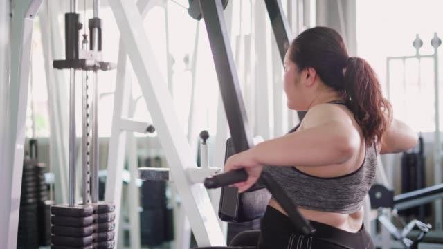 vídeos de stock, filmes e b-roll de mulher com sobrepeso usando máquina de exercício para perder peso no ginásio de fitness. - peso livre equipamento para exercícios