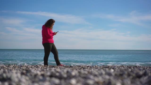 übergewichtige junge frau zu fuß und mit einem smartphone am strand, 4k video - dicke frauen am strand stock-videos und b-roll-filmmaterial