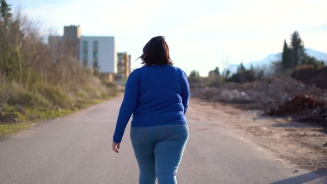 vídeos de stock e filmes b-roll de overweight young woman walking on the street - gordo