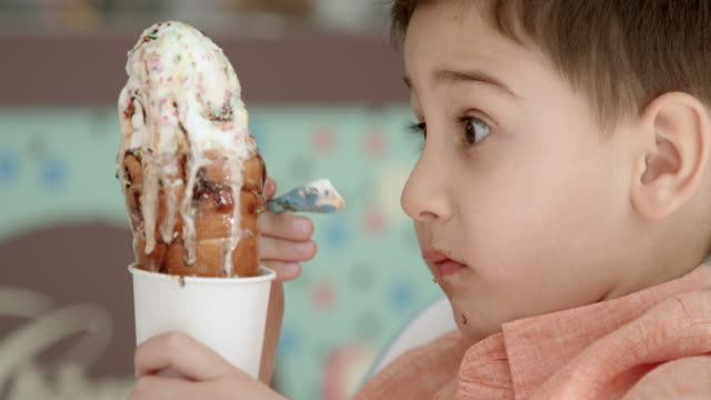 vidéos et rushes de accablé de garçon manger grand crème glacée molle avec une cuillère en plastique à la table - glace