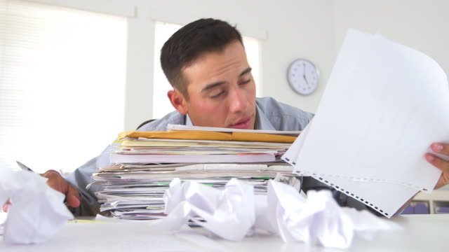overworked business man with large stack of papers - dokument stock-videos und b-roll-filmmaterial
