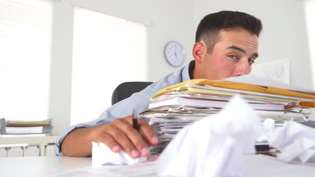 Overworked business man with large stack of papers