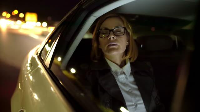ms overworked geschäftsfrau auf dem rücksitz eines taxis - after work stock-videos und b-roll-filmmaterial