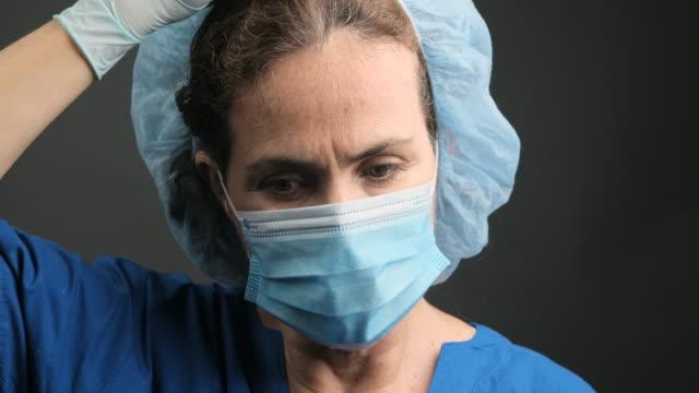 過労、女性の成熟した医療従事者は、彼女の保護顔の盾とマスクを取り除く - 盾点の映像素材/bロール