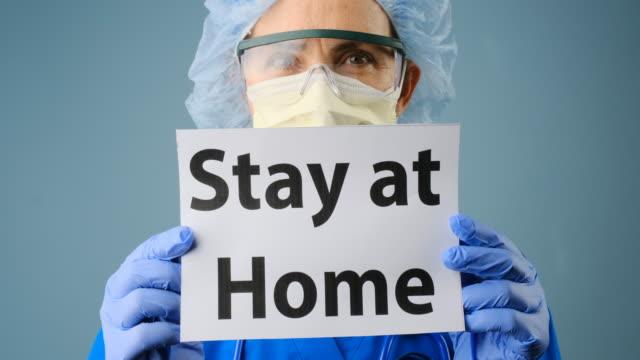 stockvideo's en b-roll-footage met overwerkte, vrouwelijke rijpe gezondheidszorgarbeider die beschermende glazen en masker draagt na een intensieve dag van het harde werk dat een teken van verblijf thuis houdt - bord bericht