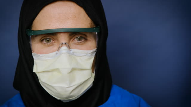 overworked, sad muslim mature female healthcare worker posing wearing a surgical mask due coronavirus - uk stock videos & royalty-free footage