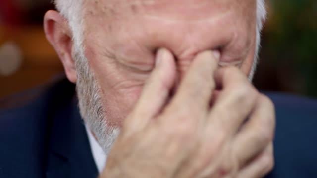 overworked senior adult businessman having a headache - market trader stock videos & royalty-free footage