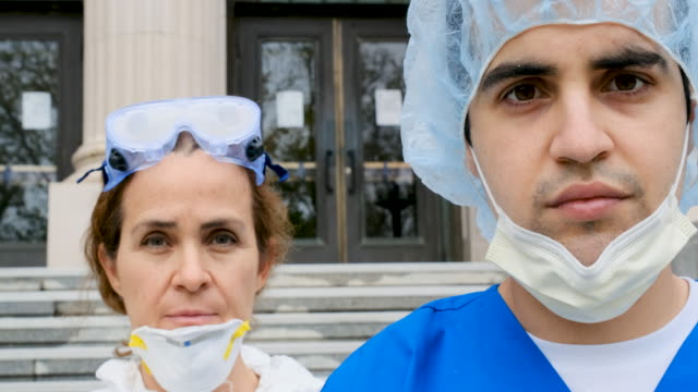 vídeos de stock e filmes b-roll de overworked, tired serious health care workers looking at the camera - enfermeiro