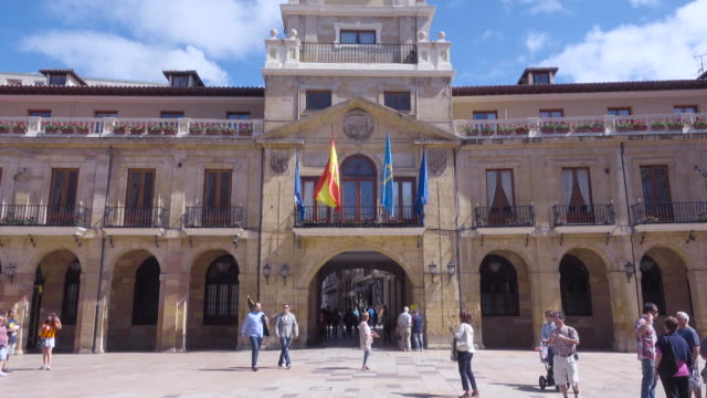 vídeos de stock e filmes b-roll de 4k | oviedo city council builinding. ayuntamiento of the city with big square. people are having a walk at this sunny day. local and spanish flags wave - patio