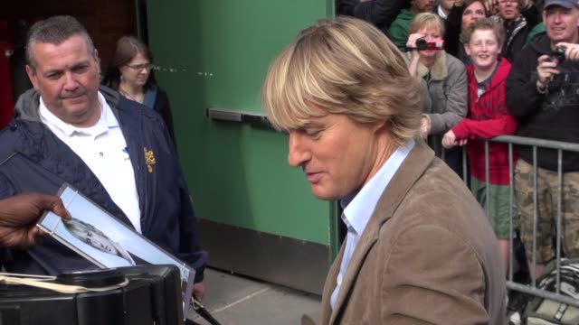 vídeos de stock e filmes b-roll de owen wilson signs autographs for fans as he departs 'good morning america' in new york 10/03/11 - autografar