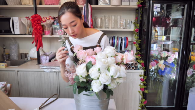 owned florist flower asian woman inside the shop to prepare for the sale, a japanese woman with professional florists, flower shops in the city, small business concept. - fioraio negozio video stock e b–roll