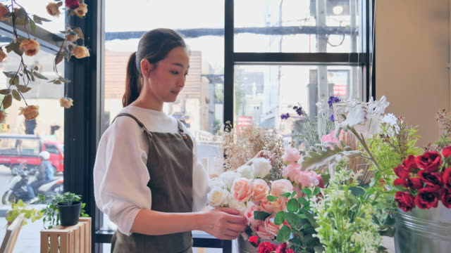 vídeos de stock e filmes b-roll de owned florist flower asian woman inside the shop to prepare for the sale, a japanese woman with professional florists, flower shops in the city, small business concept. - arranjo de flores