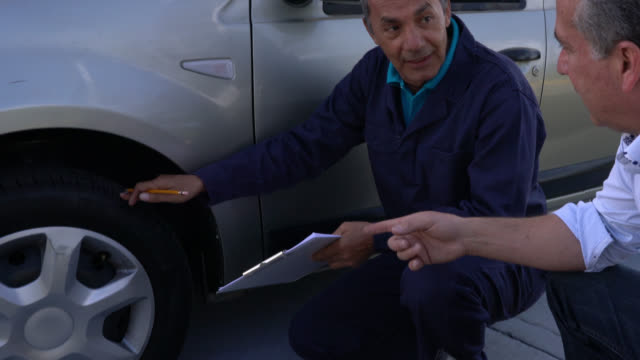 Owner of a car and mechanic talking about a flat tire